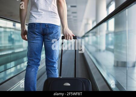 Man walking with suitcase. Rear view of traveler on moving walkway at airport terminal.