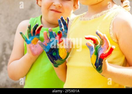 Two happy creative school age children, colorful painted hands, kids with hands covered in multi colored paint Arts and crafts, creativity, sensory in