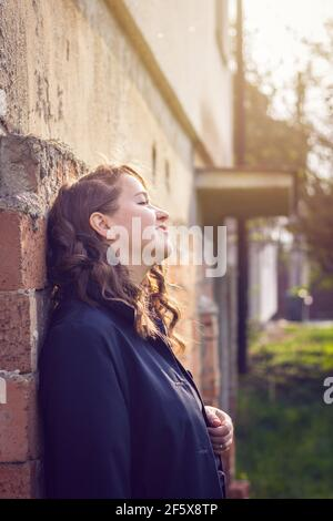 Happy brunette woman leaning brick wall and enjoying spring sunlight. Portrait of young brown hair woman