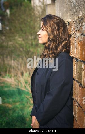 Portrait of beautiful brown hair young woman leaning wall. Stylish caucasian woman wearing black jacket