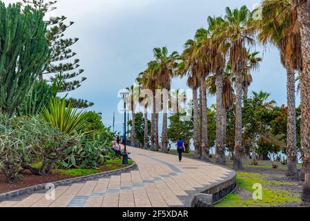 Puerto de la Cruz, Spain, Janury 3, 2021: People passing seaside promenade at Puerto de la Cruz, Tenerife, Canary islands, Spain.