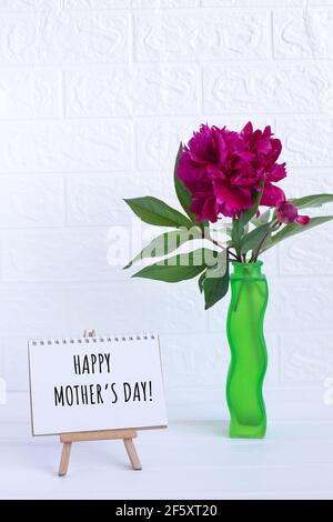 Happy Mothers day text written on notebook and one peony in vase. greeting card