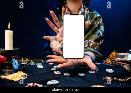 Astrology. Witch's hands hold a cellphone with a white screen. Mock up. The concept of divination and predictions with the help of modern technologies