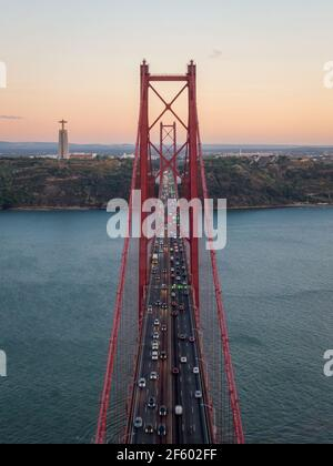 Aerial view of traffic on the April 25 Bridge (Portuguese: Ponte 25 de Abril) over the Tagus River at sunset in Lisbon, Portugal.