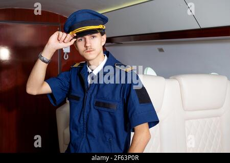 Pilot on board the plane, the cabin of a private plane, flying with comfort. Young man in a cap, crew member.