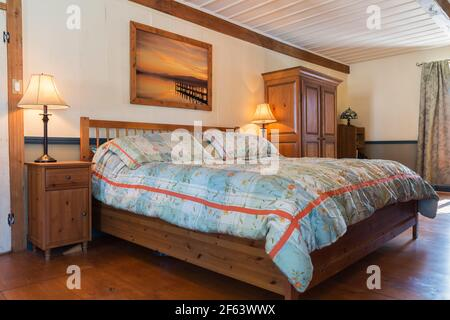King size bed on wood-frame with wooden railing headboard, dark stained pine wood nightstand and armoire in master bedroom inside an old 1825 home - Stock Photo