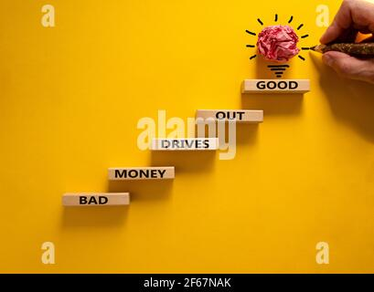 Business concept growth success process. Wood blocks stacking as step stair on yellow background, copy space. Businessman hand. Words 'bad money drive