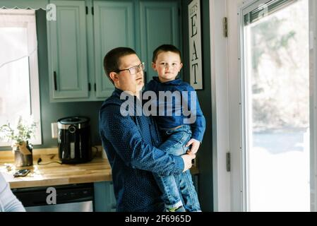 A young boy and his father standing together in kitchen looking out