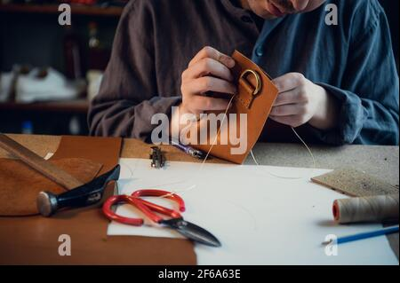 Desktop in the shoemaker workshop. The process of making leather shoes. Hands close-up without a face.