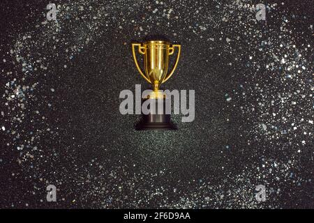 One Golden winner cup with silver sparkles on a black background. Copy space. Flat lay. Festive concept. Stock Photo