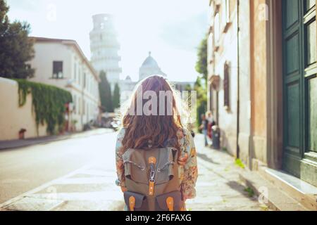 Seen from behind tourist woman in floral dress with backpack having walking tour in Pisa, Italy. Stock Photo