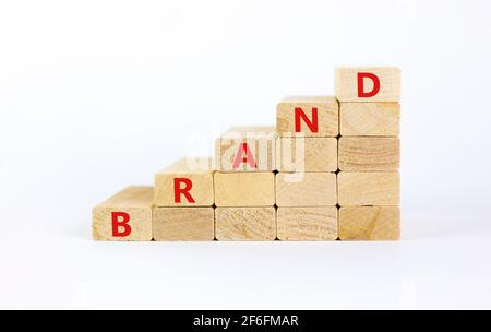 Brand symbol. Concept word 'brand' on wooden cubes on a beautiful white table. White background. Business and brand concept. Copy space.