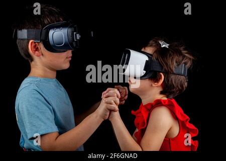 A caucasian boy and a girl wearing virtual reality headsets are playing multiplayer game. A futuristic concept with kids being in a different dimensio