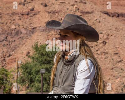 A young attractive working cowgirl wrangler on her horse on a ranch near Moab, Utah.