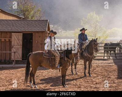 A young attractive working cowgirl wrangler and a cowboy on their horses on a ranch near Moab, Utah.