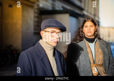 Portrait of a serious and elegant young guy wearing a flat cap. Her friend is out of focus behind. Youth and diversity concept