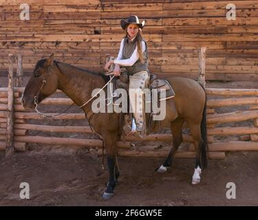 A young attractive working cowgirl wrangler poses on her horse on a ranch near Moab, Utah.  She wears leather chaps to protect her from thorny brush w