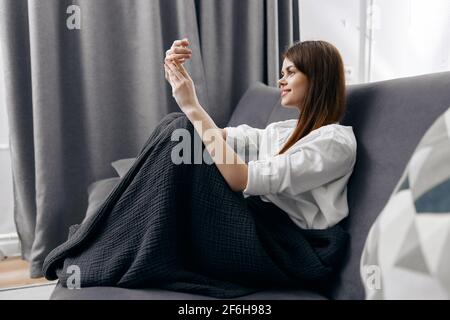 woman sitting on a gray sofa with a phone in front of her eyes side view