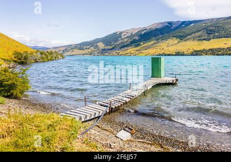 Green lakeside outdoor toilet shed standing at the end of a wooden jetty on Languna Azul, Torres del Paine National Park, Patagonia, southern Chile - Stock Photo