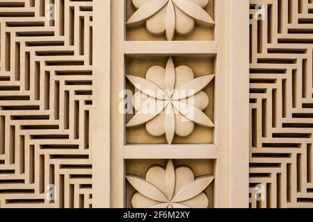 Arabic style carved stone openwork and relief, with floral patterns and geometric shapes and lines, on a building facade in Dubai JBR, UAE. - Stock Photo