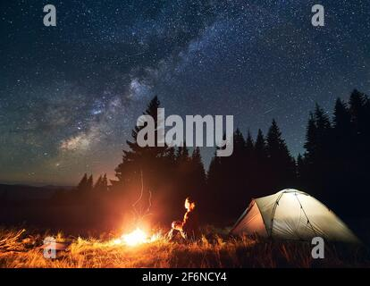 Night camping in the mountains. Young woman hiker sitting by campfire and illuminated tourist tent. On background spruce forest under beautiful night starry sky with Milky way. Concept of tourism
