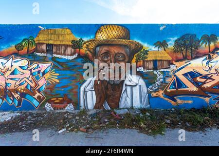 Street art in a small town on a long wall featuring an old man wearing a straw hat, a rustic hut and words, with a blue sky above the wall