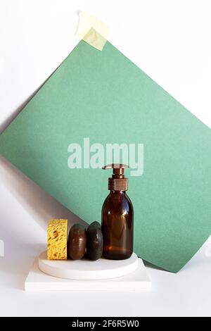 Natural handmade soap bars and organic shampoo in a glass bottle. Modern still life of body care products on white background. Sustainable lifestyle