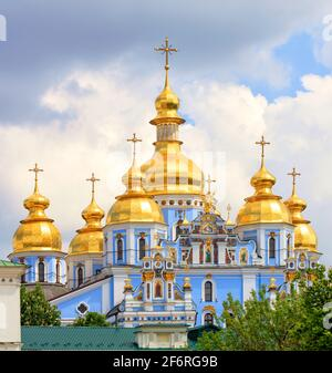 Golden domes of St. Michael's Golden-Domed Cathedral in Kiev in the spring against a blue cloudy sky on a warm spring day.