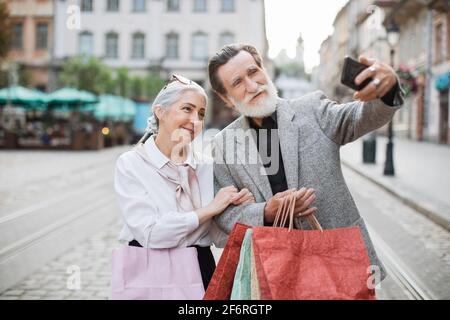 Cheerful senior couple taking selfie on modern smartphone while standing on street with shopping bags in hands. Concept of family, technology and purchase.