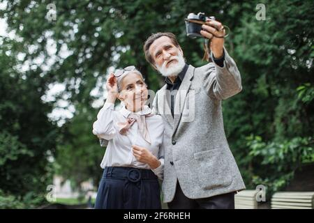 Beautiful senior family in stylish clothes taking self portrait on retro camera. Happy wife and husband standing at green park and enjoying sunny weather. Stock Photo
