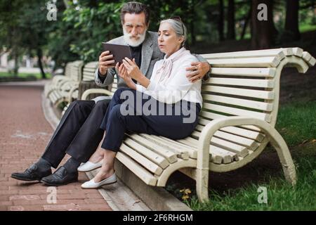 Happy mature couple using digital tablet while sitting in embrace on wooden bench. Relaxation at green park. Concept of modern technology.