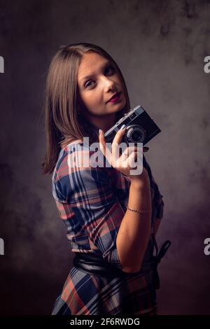 Girl photographer with retro camera, studio photography on gray background.