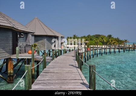 Water Villa with Wooden Pier in Sunny Maldives. Overwater Bungalow, Turquoise Lagoon and Maldivian Island Resort.
