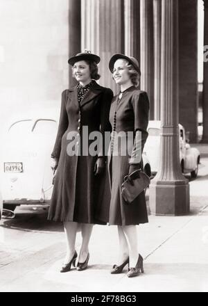 1930s 1940s TWO SMILING YOUNG WOMEN STANDING SIDE BY SIDE FULL LENGTH WEARING COATS HATS HEELS GLOVES FASHIONABLE CLOTHES - p6127 HAR001 HARS FASHIONABLE PLEASED JOY LIFESTYLE FEMALES COATS COPY SPACE FRIENDSHIP FULL-LENGTH LADIES PERSONS SIBLINGS SISTERS B&W HAPPINESS CHEERFUL STYLES PRIDE SIBLING SMILES FRIENDLY JOYFUL STYLISH FASHIONS SIDE BY SIDE SPRINGTIME YOUNG ADULT WOMAN BLACK AND WHITE CAUCASIAN ETHNICITY HAR001 HIGH HEELS OLD FASHIONED