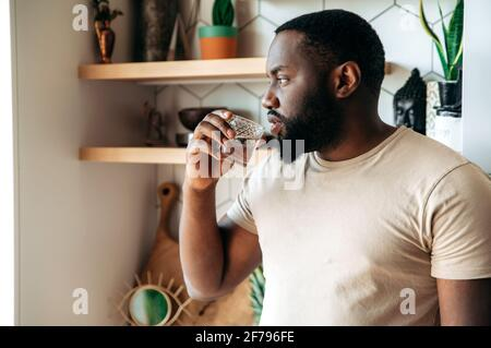 Healthy lifestyle. Handsome pensive healthy young African American bearded man, stands at kitchen, dressed in casual wear, drinks clean water from a glass, looks to the side
