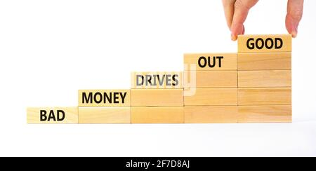 Business concept growth success process. Wood blocks stacking as step stair on white background, copy space. Businessman hand. Words 'bad money drives