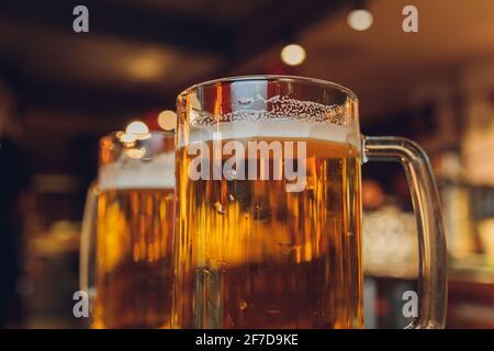 Glass of light beer on a dark pub
