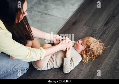 woman feeding baby food to her son, who is lying on the floor