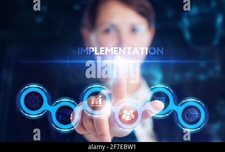 Business, Technology, Internet and network concept. Young businessman working on a virtual screen of the future and sees the inscription: Implementati