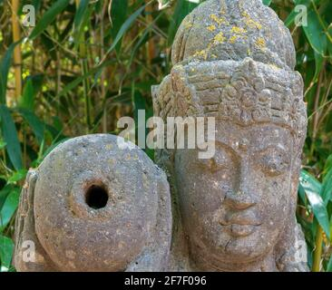 Head of a grey Buddha figure made of hewn stone with an amphora on the right shoulder. Copy space