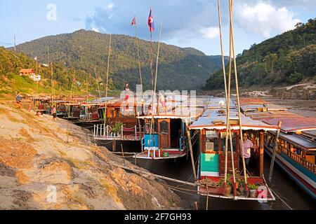Slowboats / slow boats for river cruises to Luang Phabang / Luang Prabang / Louangphabang on the Mekong River at sunset, Laos