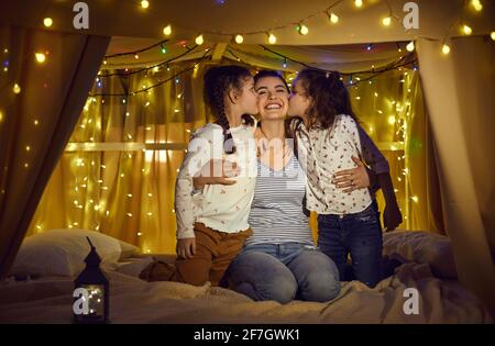 Happy daughters kissing loving mother in cheeks spend time in home tent