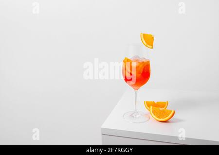 Aperol Spritz Cocktail in wine glass with ice and orange slice on white background. Long fizzy drink. Minimal creative concept.