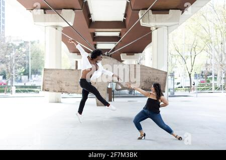 Caucasian woman and African American man dancing having fun in the city center. Space for text.