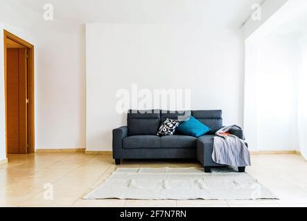 Simple sofa in a spacious room with no decoration, minimalist white walls with great lighting.