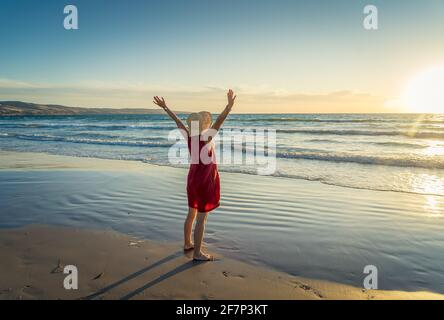 Happy attractive Mature woman in red dress enjoying outdoors and freedom on the beach, open arms outstretched with blue ocean and beautiful landscape.
