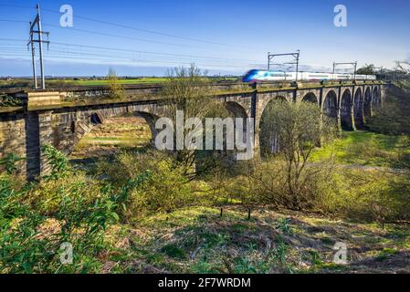 A train crossing the Sankey viaduct at Earlestown over the Sankey Valley.It is the earliest major railway viaduct in the world. Stock Photo