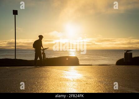 Silhouette image of a cyclist getting ready to ride on the beach at sunrise