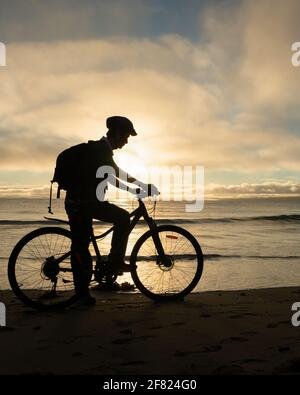 Silhouette image of a cyclist getting ready to ride on the beach at sunrise. Vertical format.