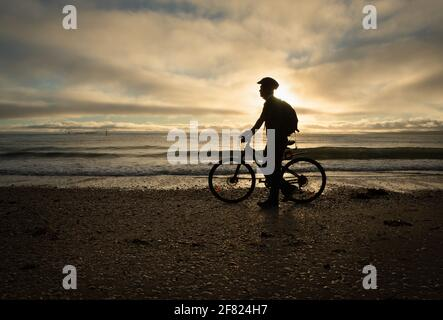 Silhouette image of a cyclist walking and pushing the bike on the beach at sunrise